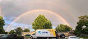 loading larsen tranfer freight under a rainbow